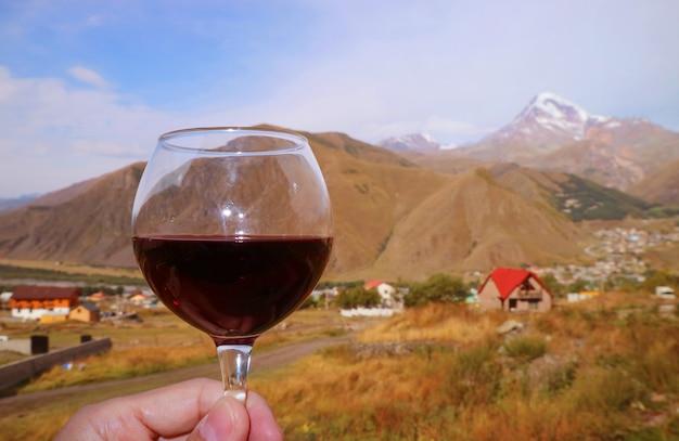 Primo piano un bicchiere di vino rosso in mano d'uomo contro le catene montuose