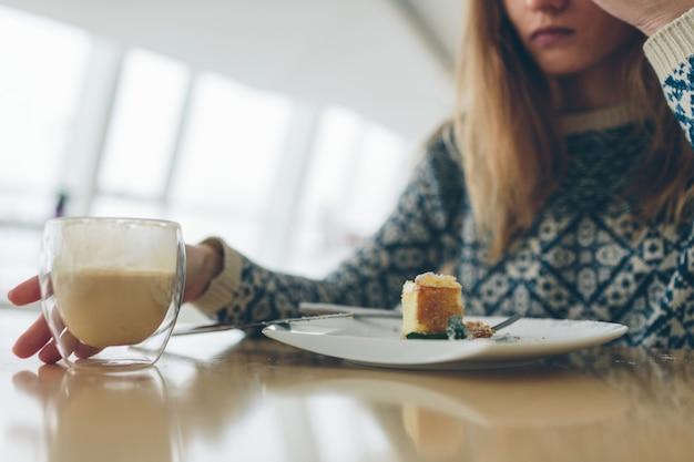 Primo piano di vetro con doppio fondo con caffè e pace di dessert e foglia di menta sul piatto bianco.
