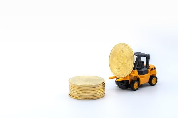 Primo piano della moneta bitcoin oro sul modello di giocattolo del carrello elevatore a forcale e pila di monete