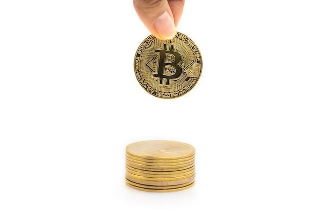 Primo piano della moneta bitcoin d'oro con il dito che tiene e che mette giù alla parte superiore della pila di monete