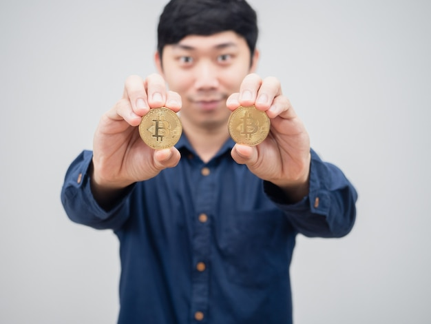 Bitcoin dell'oro del primo piano nel ritratto bianco del fondo del viso di sorriso della mano dell'uomo