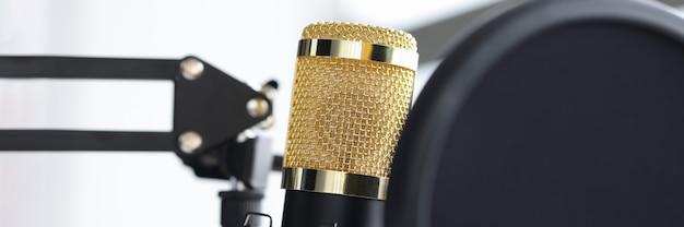 Primo piano del microfono dorato nel concetto di lavoro radiofonico dello studio di registrazione