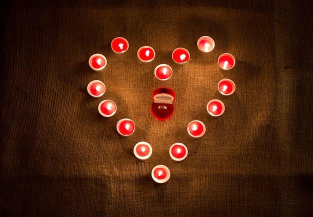 Primo piano dell'anello d'oro nella scatola che giace nel mezzo della forma del cuore delle candele