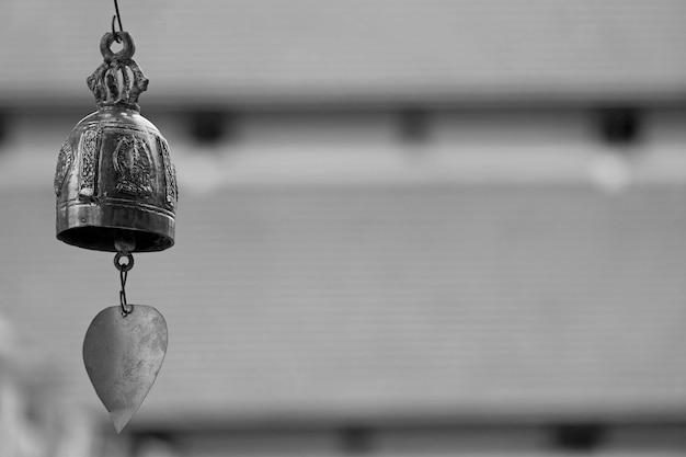 Primo piano uno splendido campanello a vento in ottone decorativo del tempio buddista contro i tetti sfocati del chiostro