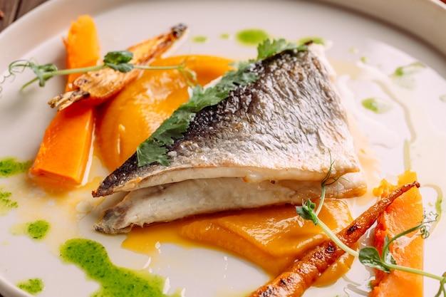 Primo piano sul pesce bianco arrosto gourmet con verdure