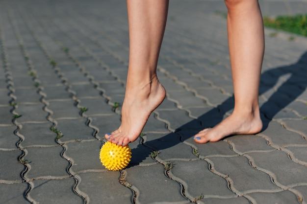 Primo piano dei piedi nudi graziosi della giovane donna che sta sulle punte dei piedi sulla palla di massaggio a spillo sulla pav...