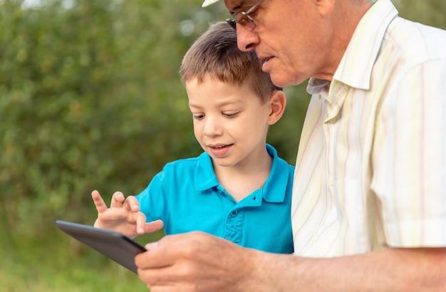 Primo piano del nipote che insegna a suo nonno a utilizzare una tavoletta elettronica sullo sfondo della natura. concetto di valori di generazione.