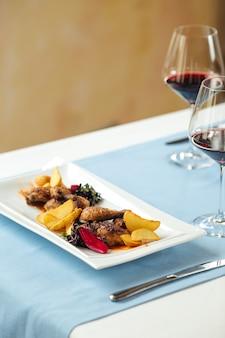 Primo piano sul pollo alla griglia con patate sul tavolo del ristorante servito