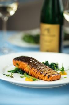 Primo piano sulla bistecca di filetto di salmone alla griglia sul tavolo blu
