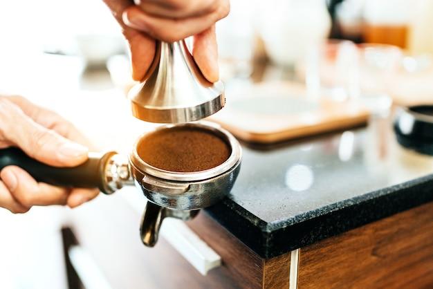 Chicco di caffè macinato del primo piano nel filtro del metallo con la maniglia che tiene dalla mano della donna