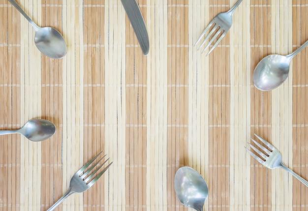 Gruppo del primo piano di cucchiaio e coltello di forchetta inossidabili sulla stuoia di legno strutturata