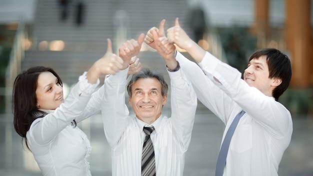 Primo piano. gruppo di mani dei giovani con i pollici in su insieme che esprimono positività, concetti di lavoro di squadra.