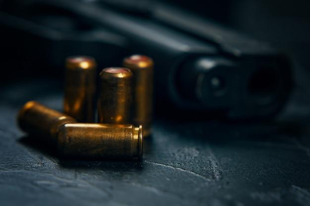 Primo piano della pistola e dei proiettili sulla pistola da tavolo per la difesa o l'attacco di armi da fuoco e munizioni...