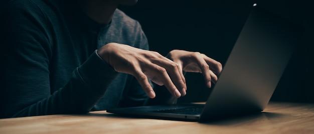 Il primo piano dell'hacker sta utilizzando il computer portatile per codificare virus o malware per l'hacking di server internet, attacco informatico, rottura del sistema, concetto di criminalità su internet.