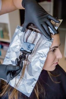 Primo piano delle mani del parrucchiere che applicano la tintura per capelli alla bella giovane donna in un salone di bellezza e dei capelli