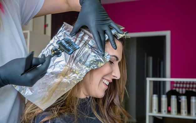 Primo piano delle mani del parrucchiere che applicano la tintura per capelli a una giovane donna felice in un salone di bellezza e capelli