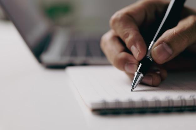 Mano del primo piano dell'uomo d'affari che scrive sul taccuino a casa, uomo d'affari che lavora al tavolo.
