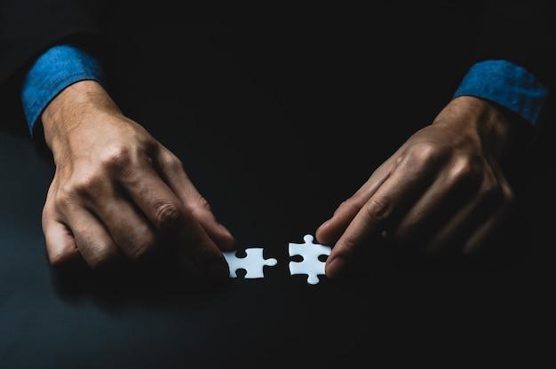 Mano del primo piano dell'uomo d'affari che collega il puzzle