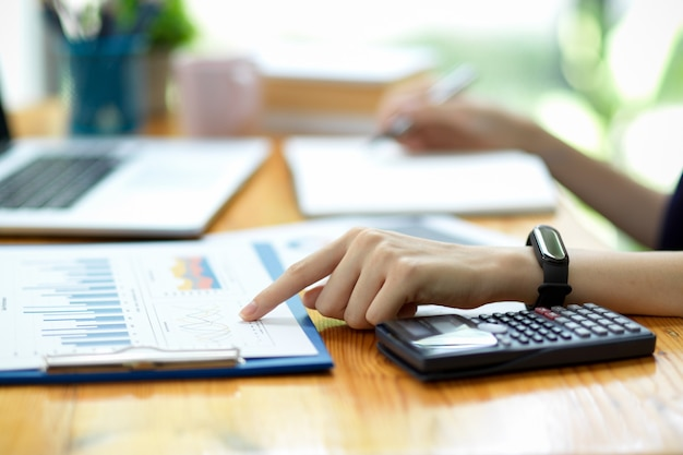Primo piano della mano di una donna d'affari o di un contabile che punta il dito indice su fogli di calcolo finanziari, rapporti di vendita, documenti aziendali in ufficio
