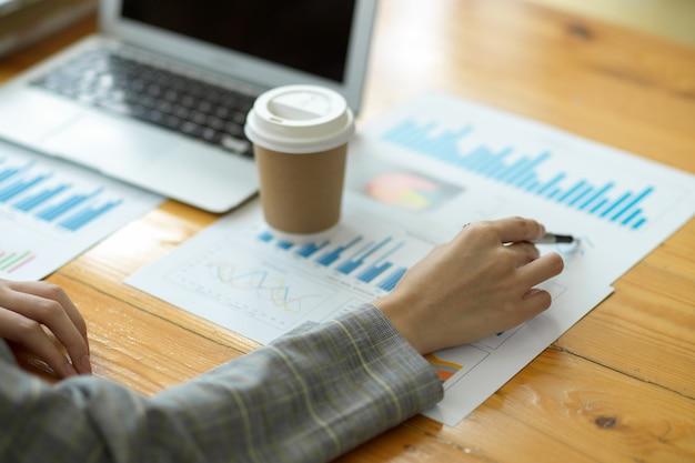Mano del primo piano, pianificazione della donna d'affari e analisi delle prestazioni di vendita aziendali dal rapporto sui dati aziendali. laptop e porta via la tazza di caffè sul tavolo, penna che punta