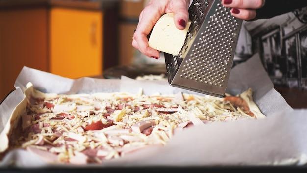 Mano del primo piano del panettiere dello chef che produce pizza fatta in casa. mani femminili che sfregano il formaggio sulla pizza