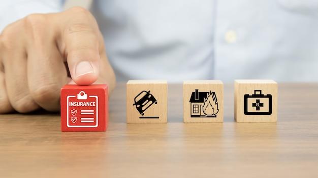 La mano del primo piano sceglie i blocchi di legno del giocattolo del cubo con l'icona di assicurazione