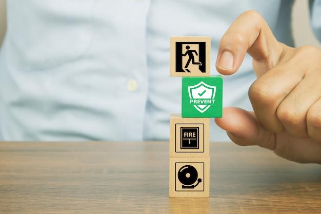 La mano del primo piano sceglie impedisce il simbolo sui blocchi di legno del giocattolo del cubo impilati con l'icona del fuoco
