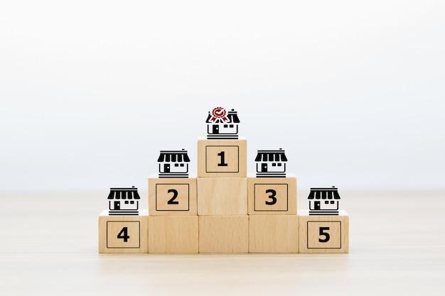 La mano del primo piano sceglie l'icona di legno del deposito di affari di franchising dei blocchi di cubo
