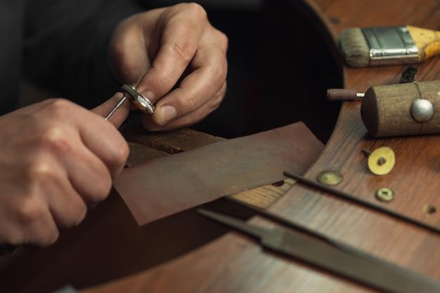 Primo piano di una mano di un orafo che lucida un gioiello prezioso con diamanti lucidi per rendere il gioiello...