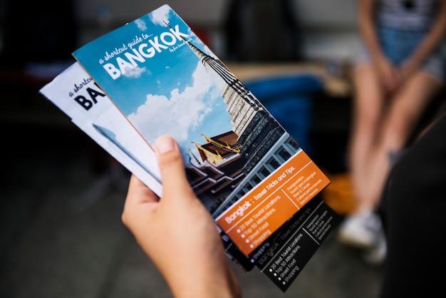 Primo piano della mano che tiene la brochure di guida turistica di bangkok