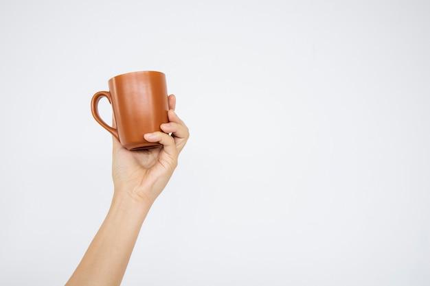 Mano del primo piano che tiene tazza di caffè nella priorità bassa bianca. tracciati di ritaglio