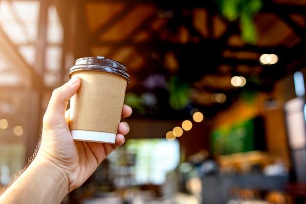Mano del primo piano che tiene la tazza di carta di caffè nella caffetteria