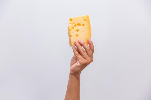 Primo piano della mano che tiene un pezzo di formaggio elementare.