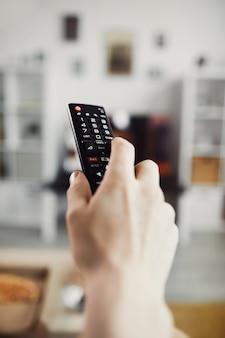 Mano del primo piano che tiene telecomando della tv