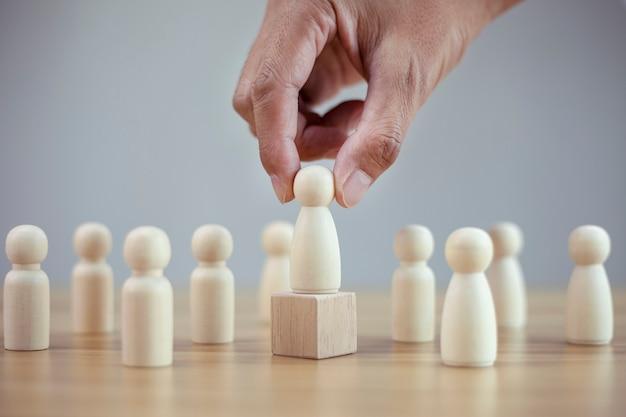 L'uomo della mano del primo piano sceglie la migliore leadership di squadra modello di persone di successo