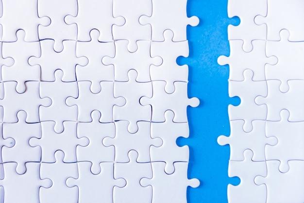 Mano del primo piano dell'uomo che collega puzzle con effetto di luce solare