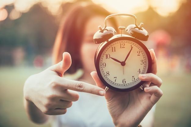 Mano del primo piano che indica ai tempi dell'orologio per è ora di fare il concetto urgente o di preavviso.