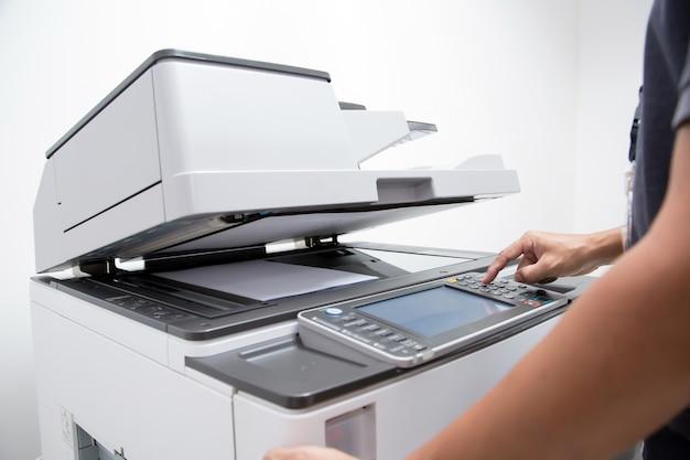Primo piano della mano premere il pulsante per utilizzare la fotocopiatrice o la macchina xerox.