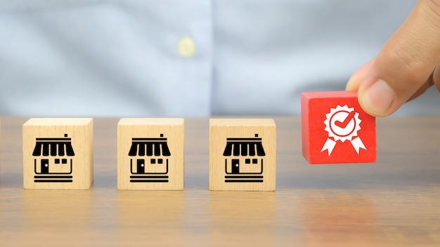 Mano del primo piano e simbolo di qualità sui cubi di legno con le icone del negozio di affari di franchising