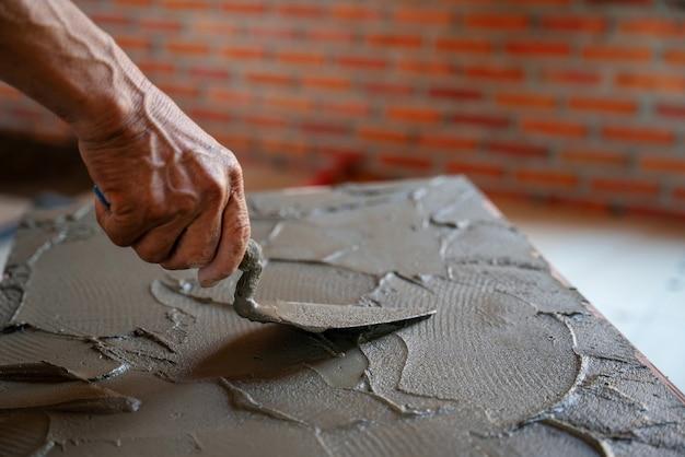 La mano del primo piano dei piastrellisti usa la malta adesiva della cazzuola per le piastrelle del pavimento per la costruzione della casa