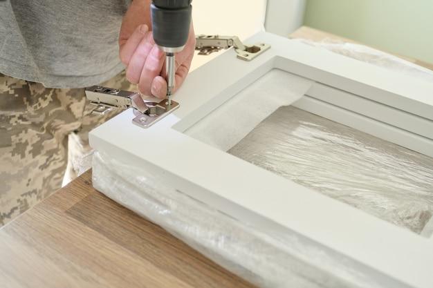 Primo piano dell'operaio che fa mobili, assemblaggio di cucina con strumenti professionali