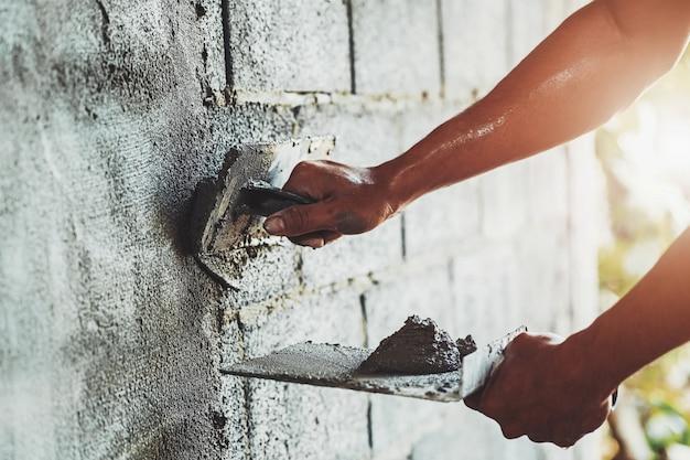 Mano del primo piano del cemento intonacante del lavoratore alla parete per la costruzione della casa