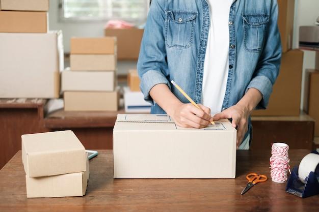 Primo piano mano di giovane donna che scrive indirizzo sulla cassetta dei pacchi per ordine di consegna al cliente, spedizione e logistica, commerciante online e venditore, imprenditore o pmi, shopping online. Foto Premium