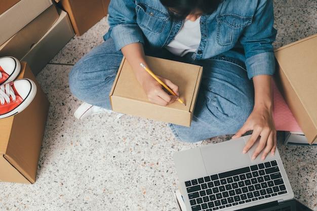 Primo piano mano di giovane donna che scrive indirizzo sulla cassetta dei pacchi per ordine di consegna al cliente, spedizione e logistica, commerciante online e venditore, imprenditore o pmi, shopping online.