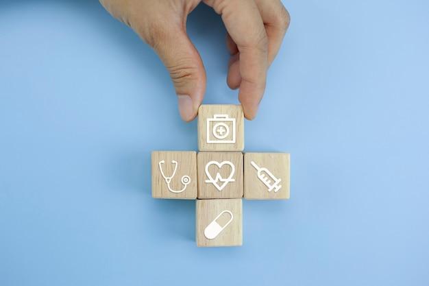 Mani del primo piano che sistemano il cubo di legno con il simbolo medico su fondo blu pastello