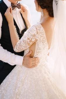 Un primo piano delle mani di una sposa che gioca con le dita con un farfallino degli sposi che lo sposo abbraccia il