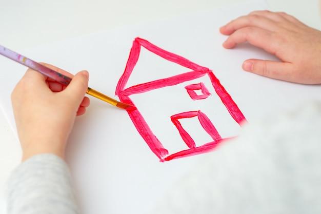 Primo piano delle mani del bambino che disegna la casa rossa con la spazzola sul foglio di carta bianco. concetto di opera d'arte.