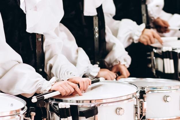 Un primo piano delle mani di un batterista in una parata. completo da bambino in camicie bianche. nuovo rullante bianco, bastoncini bianchi. il concetto di una parata e una marcia militari.