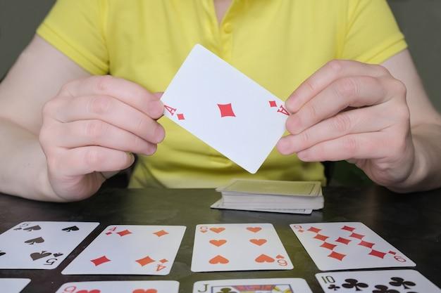 Primo piano delle mani che tengono asso di quadri. la donna sul tavolo sta giocando al solitario. giochi da tavolo e di carte, attività per il tempo libero a casa.
