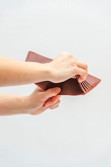 Primo piano delle mani che tengono il portafoglio in pelle marrone senza soldi